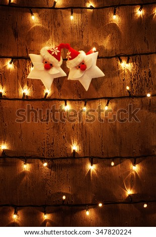 Photo of abstract Christmas glowing background, yellow electrical garland on old wooden door, shiny decorations on dark grunge wall, two Santa Claus stars, New Year festive ornament - stock photo