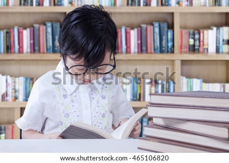 Photo of adorable female elementary school student reading books on the table in the library