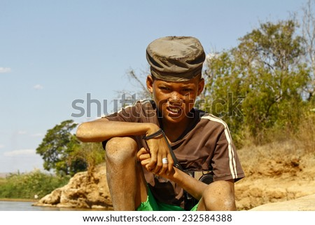 Photo of adorable young happy boy - african poor child on the river - stock photo