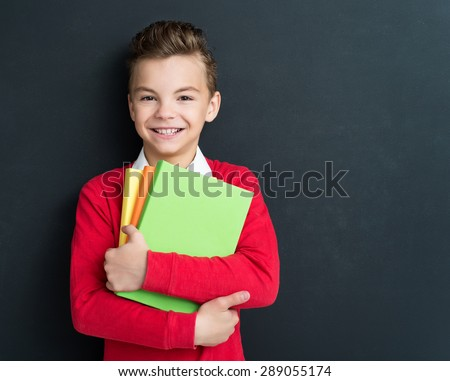 Photo of adorable young happy boy with books at the black chalkboard in classroom. - stock photo