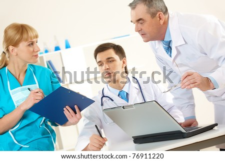 Photo of aged physician and young clinician looking at document in nurse?s hand
