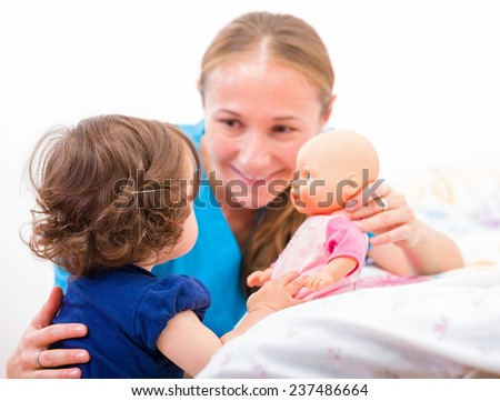 Photo of an adorable baby with her babysitter - stock photo