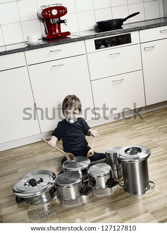 Photo of an adorable young boy using wooden spoons to bang pots and pans that are set up like a drumset. Desaturated and contrast increased. - stock photo