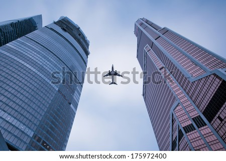 Photo of an airplane above the glass office buildings. - stock photo