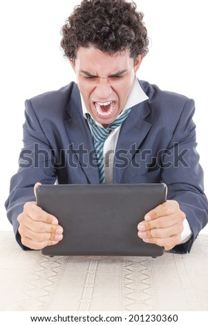 Photo of an angry and pissed off caucasian business male frustrated with work sitting in front of laptop with his hands trying to break laptop - stock photo
