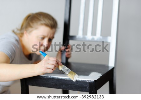 Photo of an attractive woman painting the chairs in the room