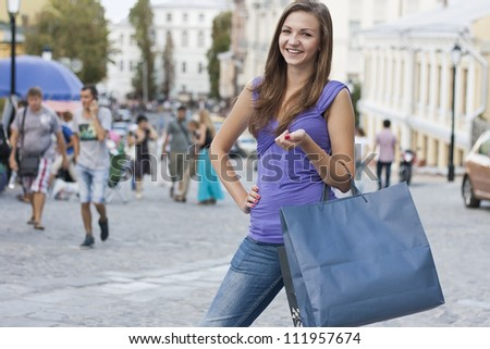 Photo of an attractive young woman holding up shopping bags - stock photo