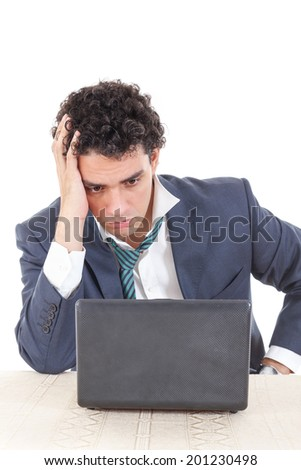 Photo of an caucasian business male frustrated with work sitting in front of a laptop with his hand on head - stock photo