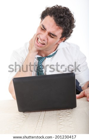 Photo of an desperate caucasian business man frustrated with work sitting in front of a laptop with his hand on neck. Stiffness, back pain and neck pain because overtime at work