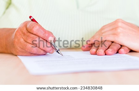 Photo of an elderly woman sign the testament - stock photo