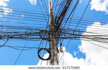 Photo of an electric pole with a many cables on sky background