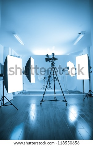 Photo of an empty photographic and video studio with modern lighting equipment. Color processed