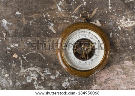 Photo of an old barometer on wooden background texture - stock photo