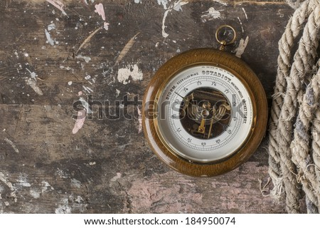 Photo of an old barometer on wooden background texture with a rope - stock photo