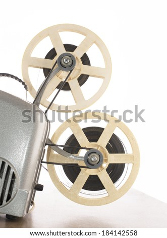 photo of an old movie projector isolated on white background on wooden table - stock photo