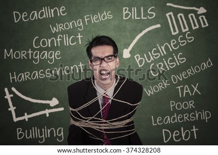Photo of angry businessman tied with rope in the classroom and shouting at the camera - stock photo