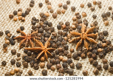 Photo of anise and black pepper on sacking background