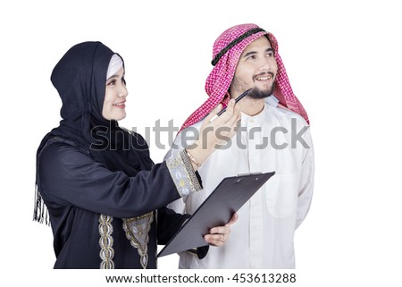 Photo of Arabian female entrepreneur showing something at her partner while holding a clipboard