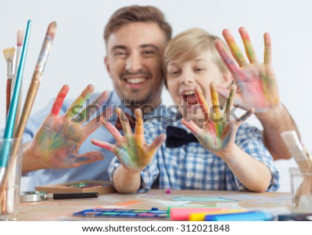 Photo of art teacher and schoolboy with color on hands - stock photo