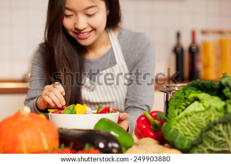 photo of asian young woman composing a colorful salad at home in the kitchen