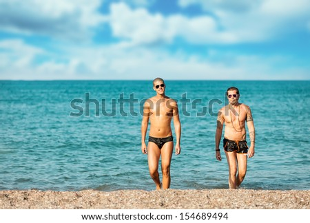 Photo of attractive gay couple at the beach  - stock photo