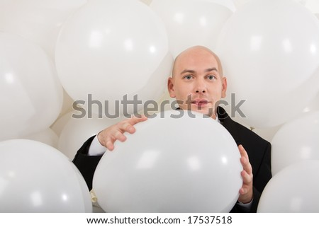 Photo of attractive male holding big white balloon in hands and looking at camera - stock photo