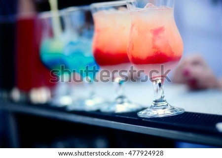 photo of Bartender preparing a cocktail with blue and red syrup