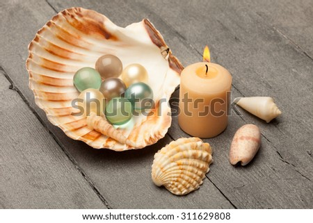 Photo of bath pearls in a shell over wooden table - stock photo