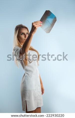 Photo of beautiful adult blonde nurse looking at x-ray photo in studio