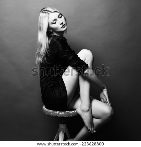 Photo of beautiful blonde woman in black dress. Fashion photo. Black and white - stock photo