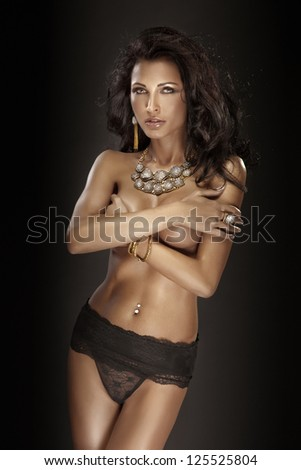 Photo of beautiful brunette in black panties and amazing jewelry - stock photo