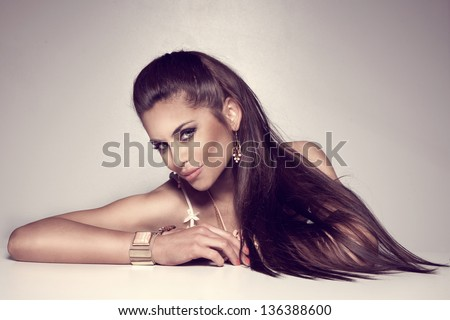 Photo of beautiful brunette woman with long hair wearing a lot of jewelry.