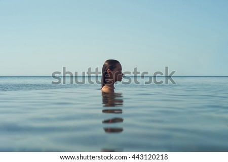 Photo of beautiful elegant woman in the sea at sunset - stock photo