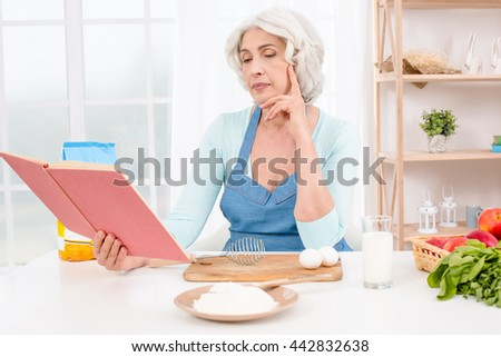Photo of beautiful emotional adult woman. Nice kitchen with window. Woman reading recipe - stock photo