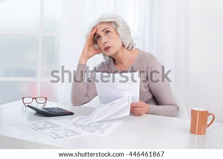 Photo of beautiful emotional adult woman. White interior with window. Upset woman working with bills