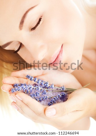 Photo of beautiful girl smell purple lavender flowers, closeup portrait of cute woman with closed eyes and holding sea salt and violet flower in hands, pretty female with clean skin, spa concept - stock photo