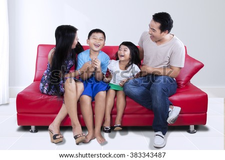 Photo of beautiful happy family sitting on the couch while having fun and laughing together at home