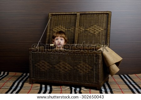 photo of beautiful little girl sitting in suitcase