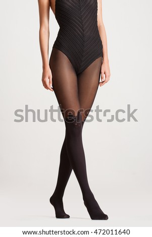 Photo of beautiful long slender legs in black stockings.
