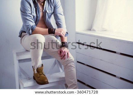 photo of Beautiful muscular male model seat close to the window - stock photo