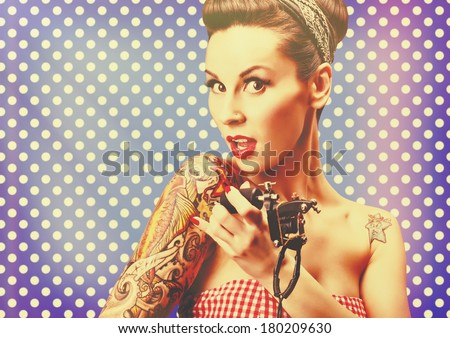 Photo of beautiful pin-up girl with tattoos, tattooing herself and looking at the camera against blue polka dot background. Retro styled imagery, grungy, toned image, noise added, vintage. - stock photo