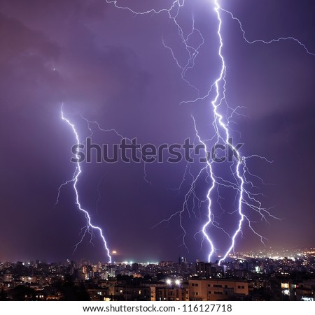 Photo of beautiful powerful lightning over big city, zipper and thunderstorm, abstract background, dark blue sky with bright electrical flash, thunder and thunderbolt, bad weather concept - stock photo