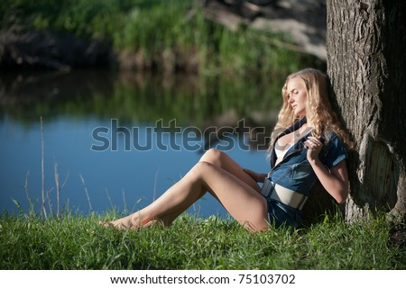 Photo of  beautiful sexy girl with long legs rests to lean one's ellbows on tree, pleasure in the sun with closed eyes, outdoor near forest lake
