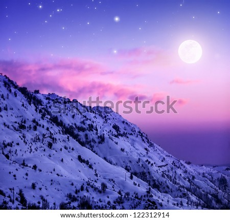 Photo of beautiful snowy mountains on purple sunset background, Faraya mountain in Lebanon covered with white snow, wintertime cold weather, moonlight in dark night, winter holidays concept - stock photo