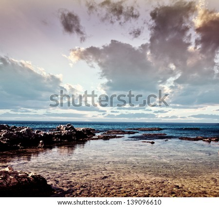 Photo of beautiful stony coast, rocky beach, dramatic sunset, cloudy sky, stunning seascape, summertime vacation, travel and tourism concept - stock photo