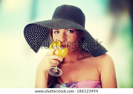 Photo of beautiful woman holding a orange cocktail  - stock photo
