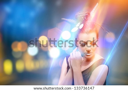 photo of beautiful woman standing in a colorful city