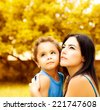 Photo of beautiful woman with little son on backyard in autumn, portrait of mother hugging adorable baby boy, young family playing games in autumn park, happy childhood, love concept - stock photo