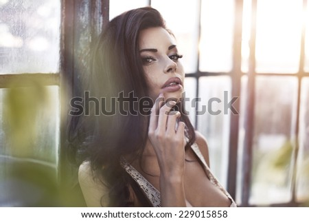 Photo of beautiful young brunette girl smiling, posing with her hands in hair.  - stock photo