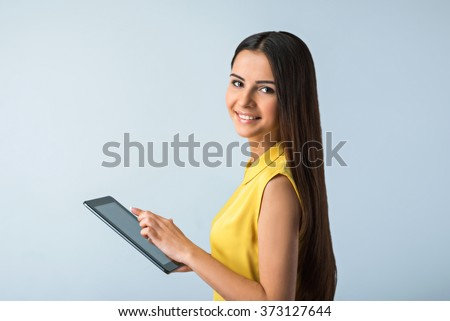 Photo of beautiful young business woman standing near gray background. Smiling woman with yellow shirt using tablet computer and looking at camera - stock photo